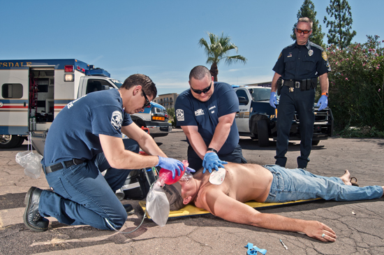In the setting of a cardiac arrest, CPR takes priority over naloxone.