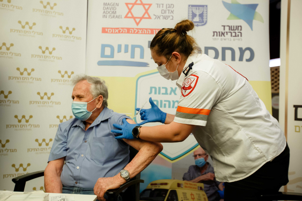 A nursing home resident is vaccinated by a Magen David Adom paramedic.
