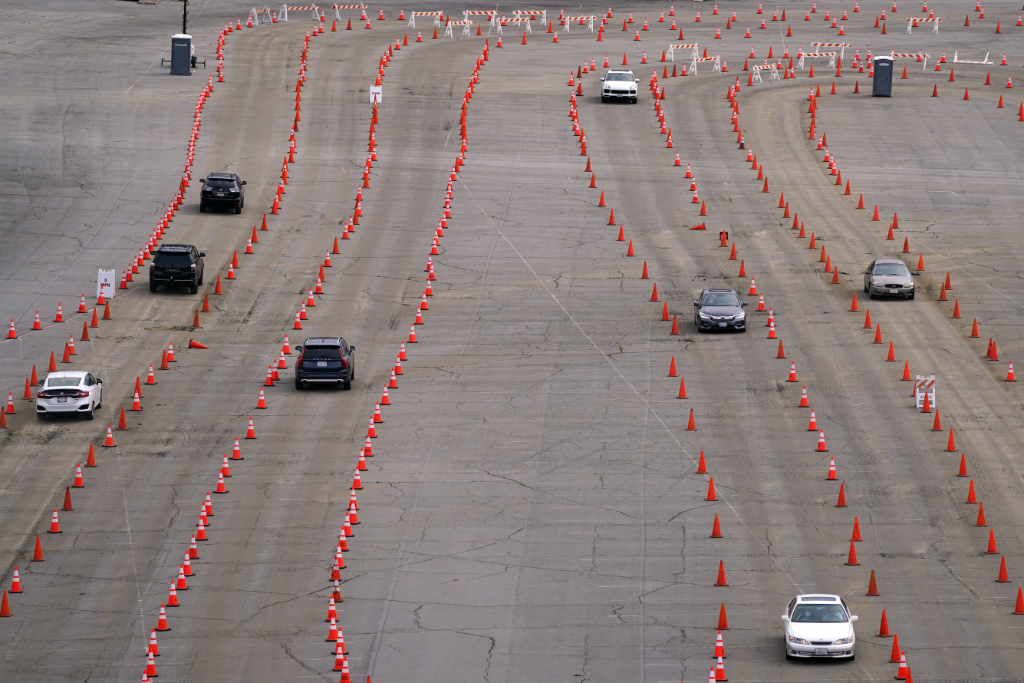 FILE - In this Feb. 1, 2021, file photo, light traffic flows through cones as people arrive at the Dodger Stadium parking lot to receive the COVID-19 vaccine in Los Angeles. About 1 in 3 Americans say they definitely or probably won't get the COVID-19 vaccine, according to a new poll from The Associated Press-NORC Center for Public Affairs Research.