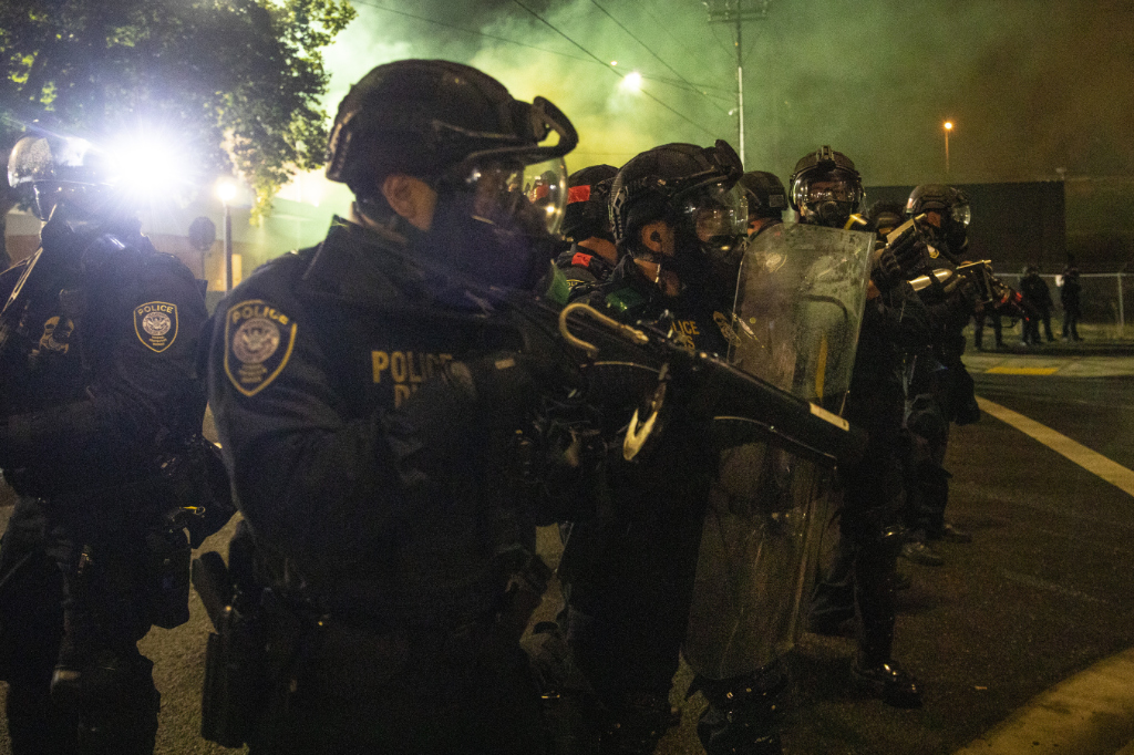 FILE - In this Sept. 18, 2020, file photo, tear gas fills the air as police take control of the streets during protests in Portland, Ore. An Oregon lawmaker is seeking to ban the use of tear gas and other agents against crowds of people in one of the most sweeping police measures in the country regarding crowd control devices.
