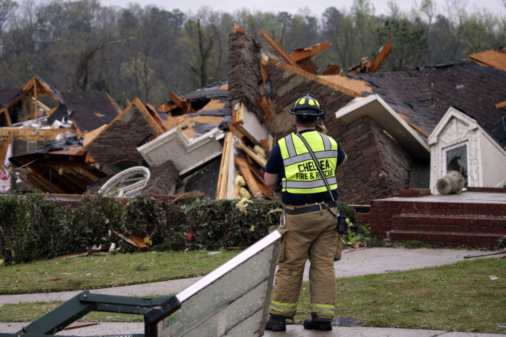 A firefighter surveys damage to a house where the family was trapped, but were able to get out after a tornado touches down south of Birmingham, Ala.