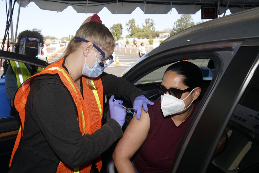 In this March 2, 2021, file photo, Vanessa Guerra, at right, a special education teacher at Grant Elementary School in Hollywood, receives a shot of the Moderna COVID-19 vaccine from nurse Kelly Mendoza.