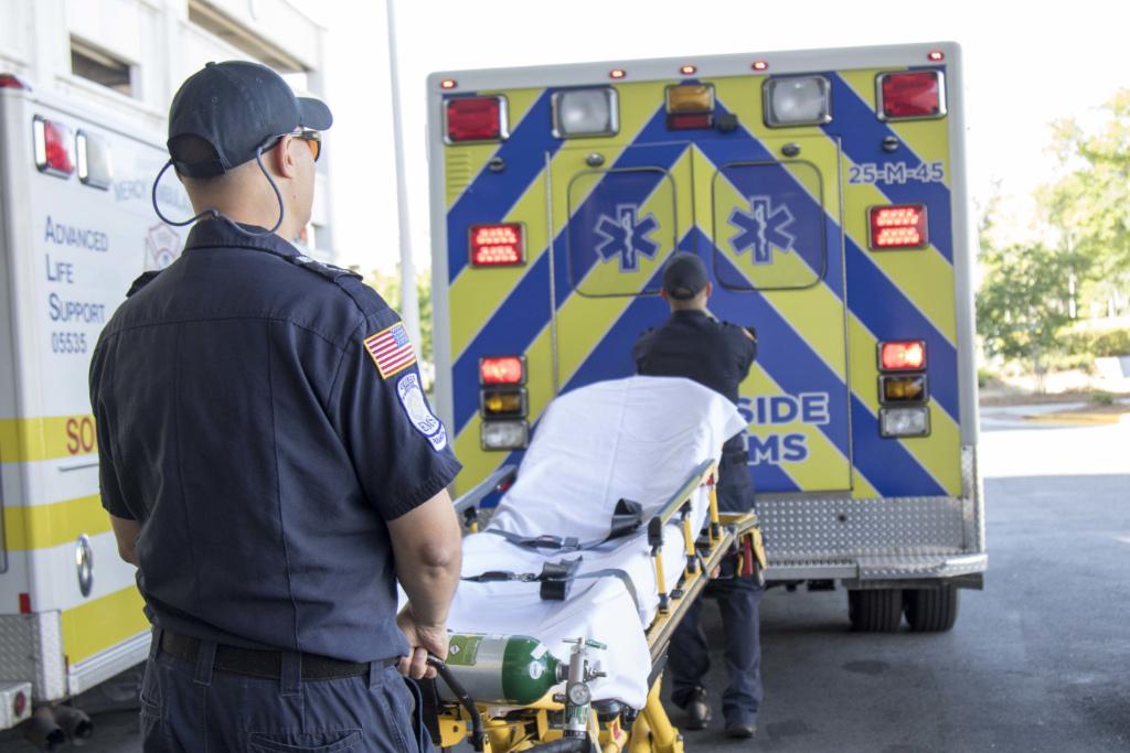 A paramedics wheels a stretcher by an ambulance.