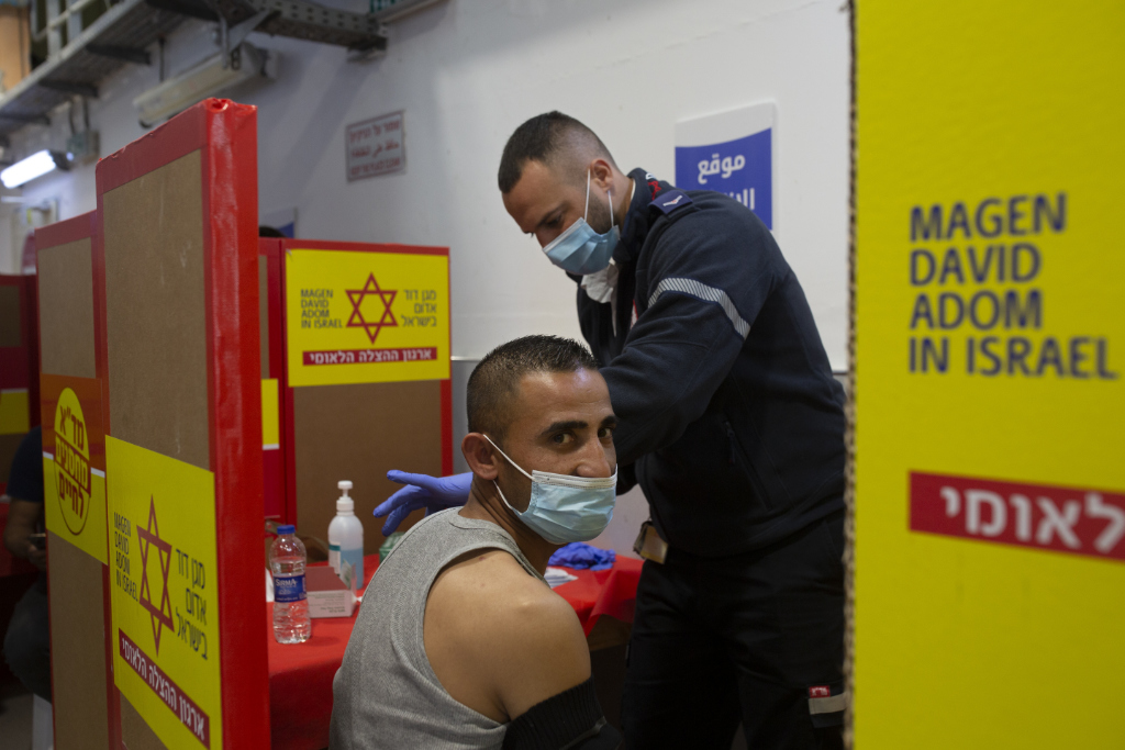 A Palestinian worker receives the Moderna coronavirus vaccine at the Hashmonim checkpoint between the West Bank and Israel, near the Israeli West Bank settlement of Nili, Monday, March 8, 2021.
