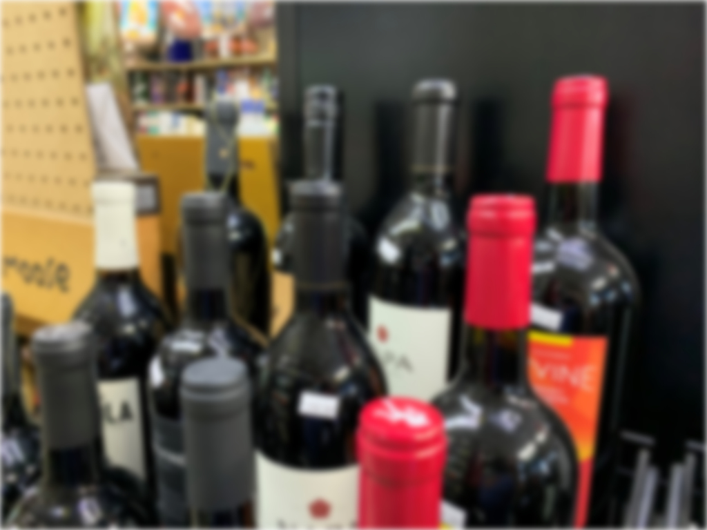The photo shows blurred wine bottles