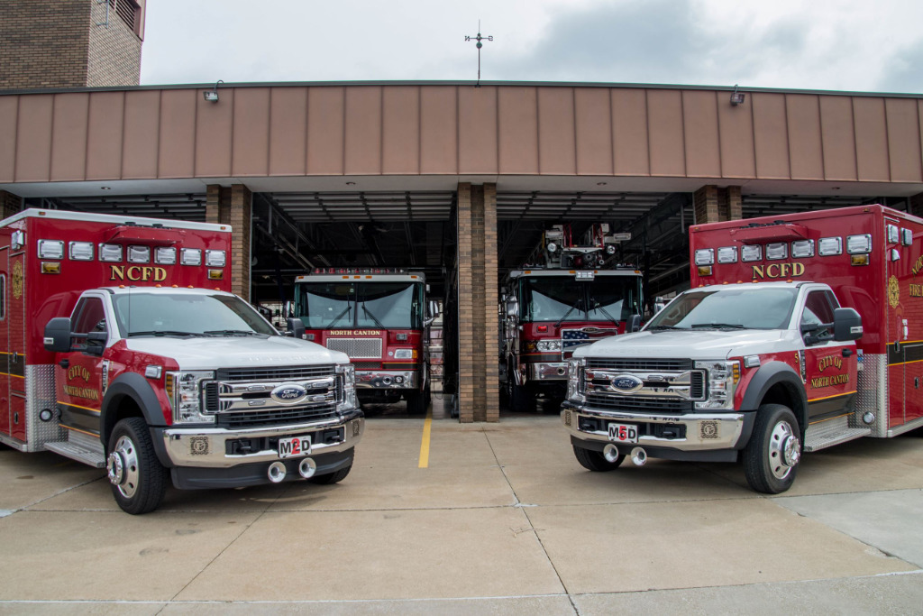 The photo shows ambulances parked outside a fire station.