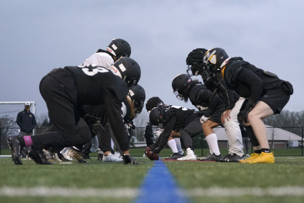In this Tuesday, Feb. 2, 2021, file photo, university football players wait for the snap on the line of scrimmage during practice in Tacoma, Wash.