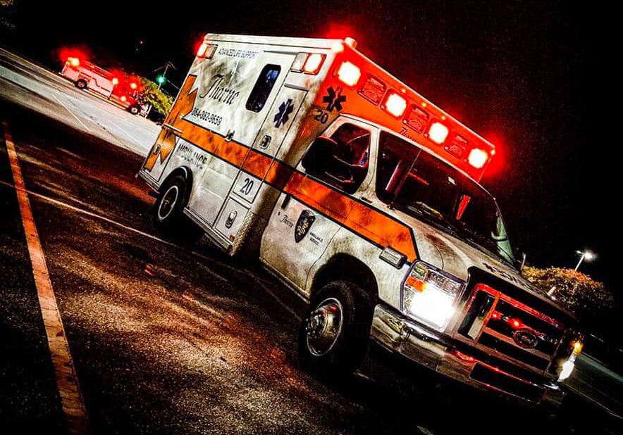 The photo shows a Thorne Ambulance at night with its emergency lights activated.