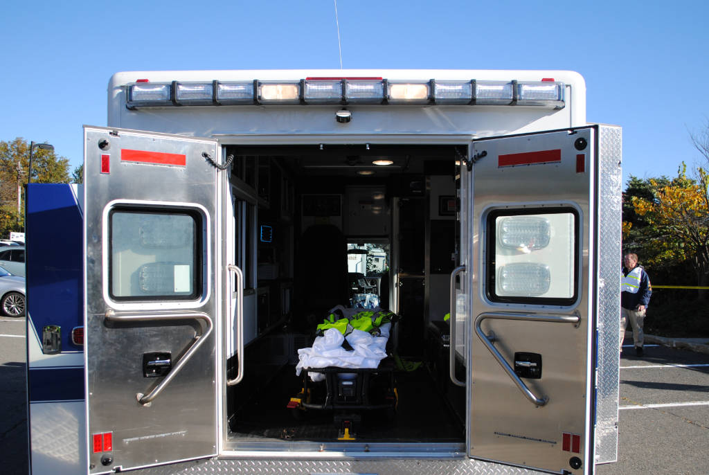 The photo shows the back of an ambulance with its doors open.