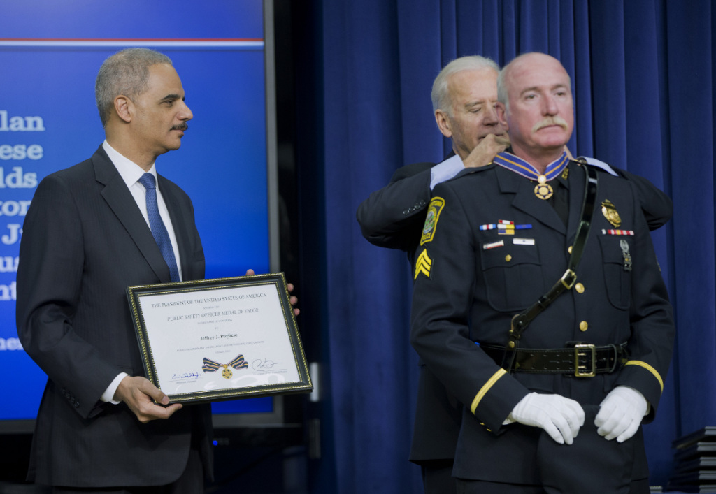In this Feb. 11, 2015, file photo, Attorney General Eric Holder and Vice President Joe Biden award the Medal of Valor to Sgt. Jeffrey Pugliese from the Watertown, Mass., Police Department, during a ceremony in the Old Executive Office Building at the White House Complex in Washington.