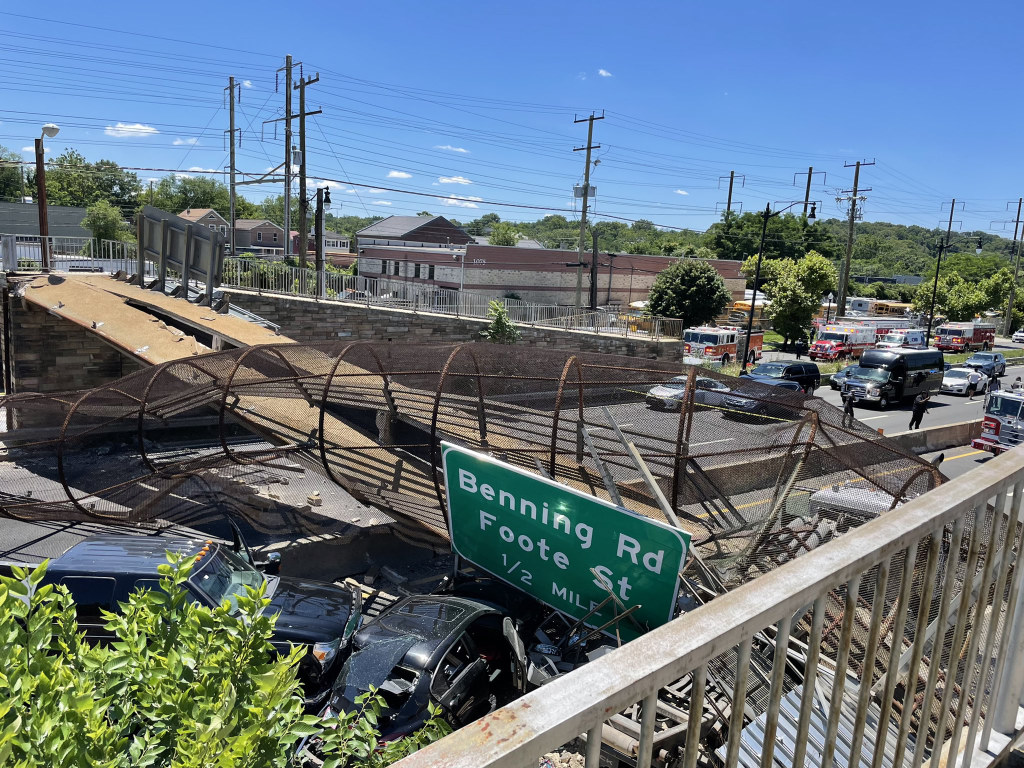 Cars are mangled after a pedestrian bridge collapsed on top of them.