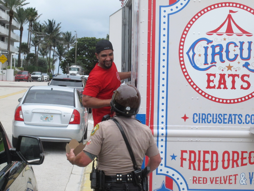 Robert Martinez talks with a law enforcement officer after handing him a hot meal from his food truck in Surfside, Fla., Tuesday, June 29, 2021.