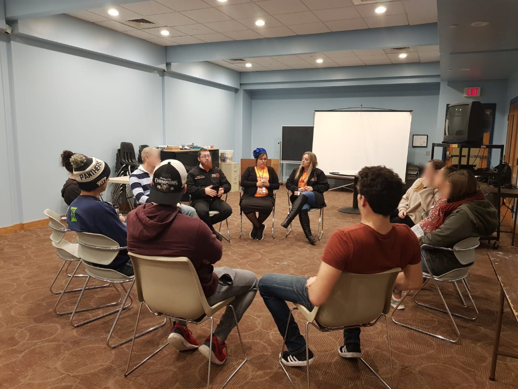 Einat Kauffman (right of center) and Hadass Rucham (center), together with other members of the PCRU, hold a therapy session for the community in Pittsburgh following the Tree of Life shooting.