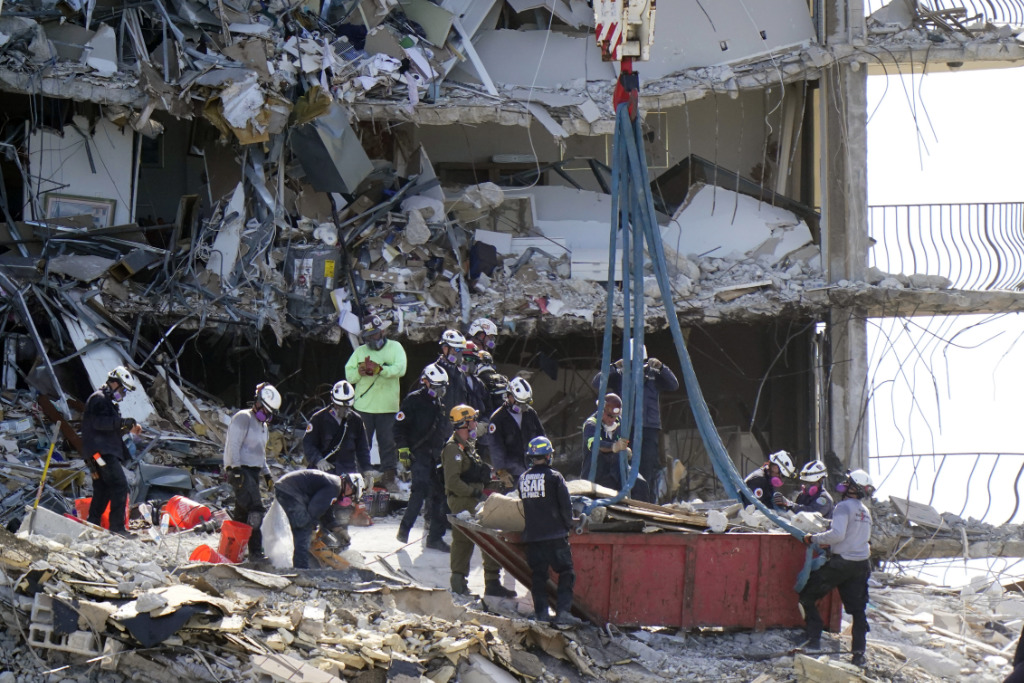 Search and rescue personnel search for survivors through the rubble at the Champlain Towers South in Surfside, Fla., Sunday, June 27, 2021.