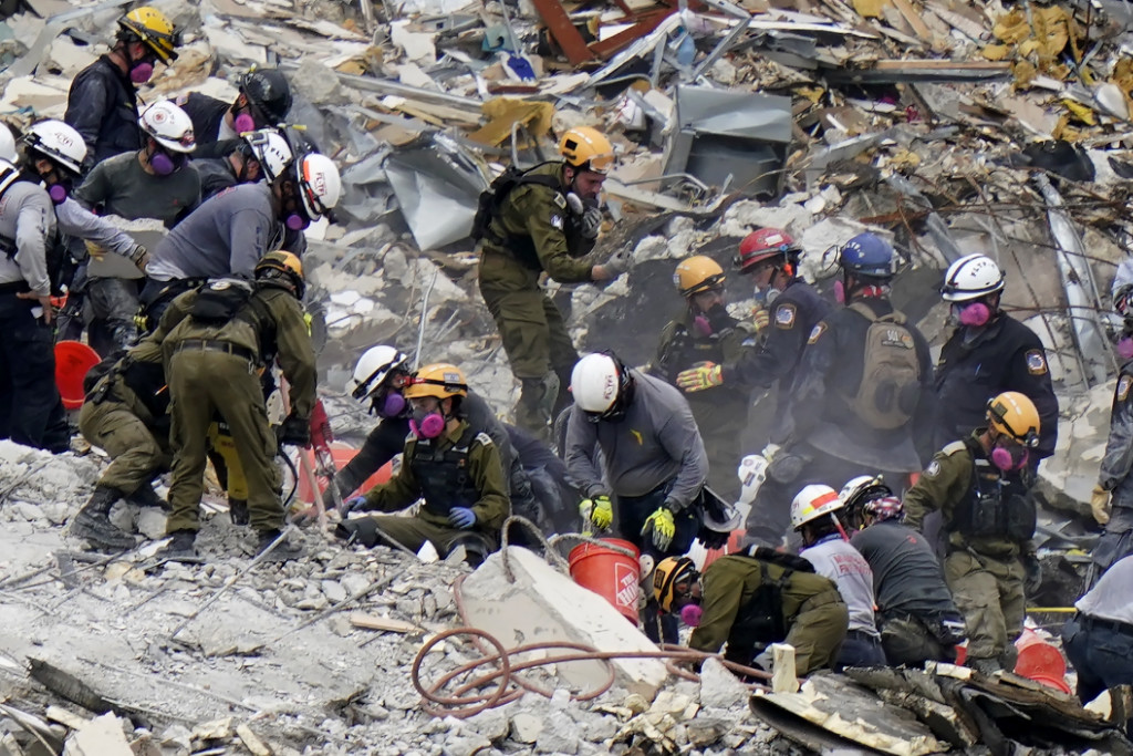 Workers search the rubble at the Champlain Towers South Condo in Surfside, Fla.