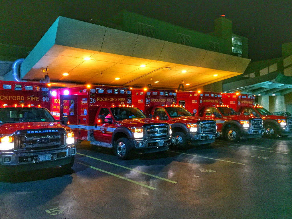 The photo shows several ambulances lined up outside a building.