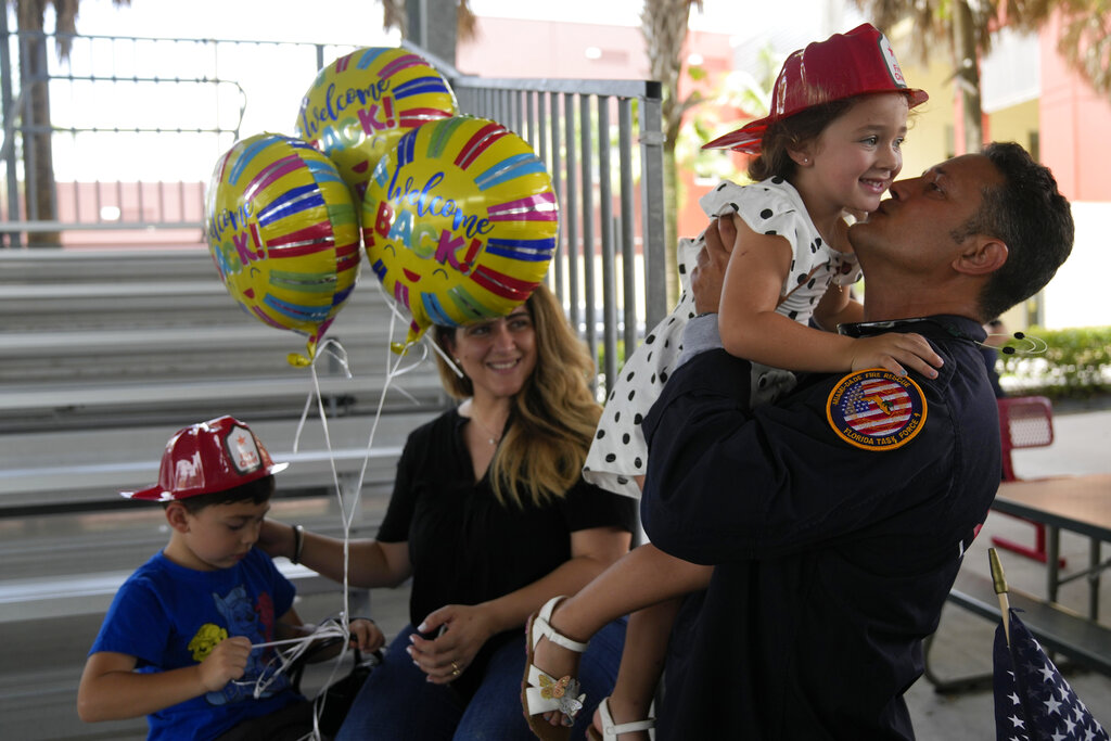 Capt. Eric Hernandez lifts up his daughter Isabella, 3, as his wife Yaimara and son Eric, 4, look on, as members of Miami-Dade Fire Rescue's urban search and rescue team are reunited with their families after weeks of working on the rubble pile at the collapsed Champlain Towers South condominium, on Friday, July 23, 2021, in Doral, Fla.