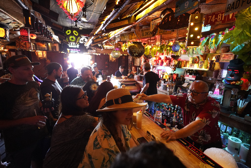 Patrons enjoy cold tropical cocktails in the tiny interior of the Tiki-Ti bar as it reopens on Sunset Boulevard in Los Angeles.