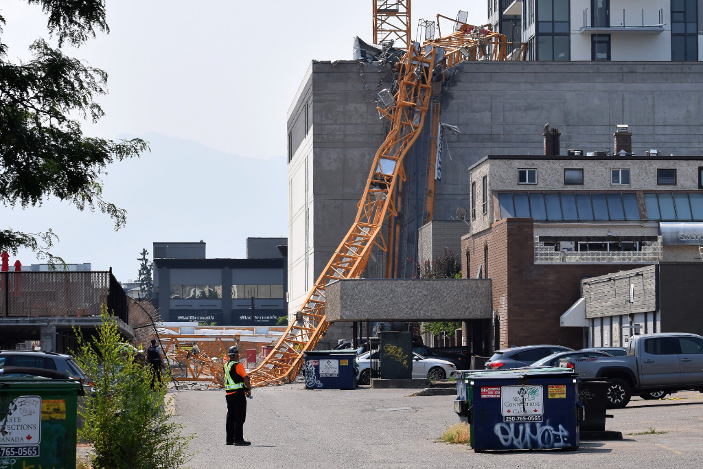 A worker looks on as a police officer investigates a collapsed crane resting on the building it damaged in Kelowna, Brith Columbia, Monday, July 12, 2021.