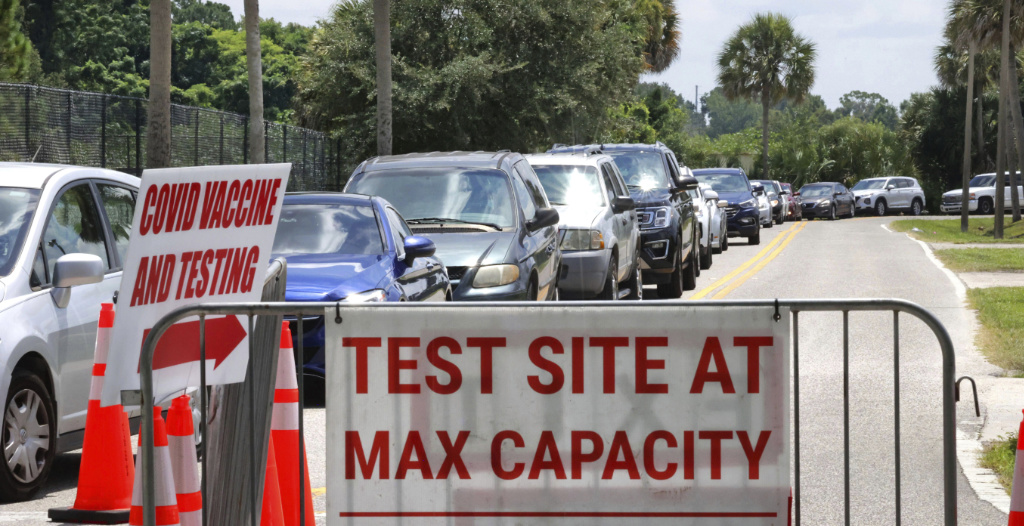 Signage stands at the ready (foreground) in case COVID-19 testing at Barnett Park reaches capacity, as cars wait in line in Orlando, Fla., Thursday, July 29, 2021.