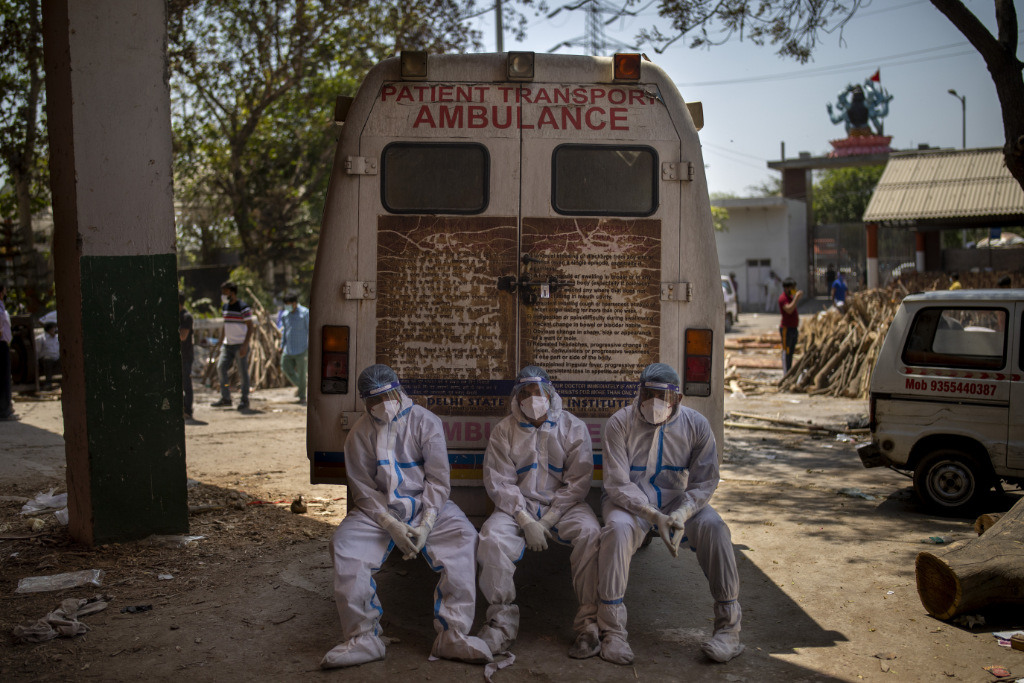 Exhausted workers, who bring dead bodies for cremation, sit on the rear step of an ambulance inside a crematorium.
