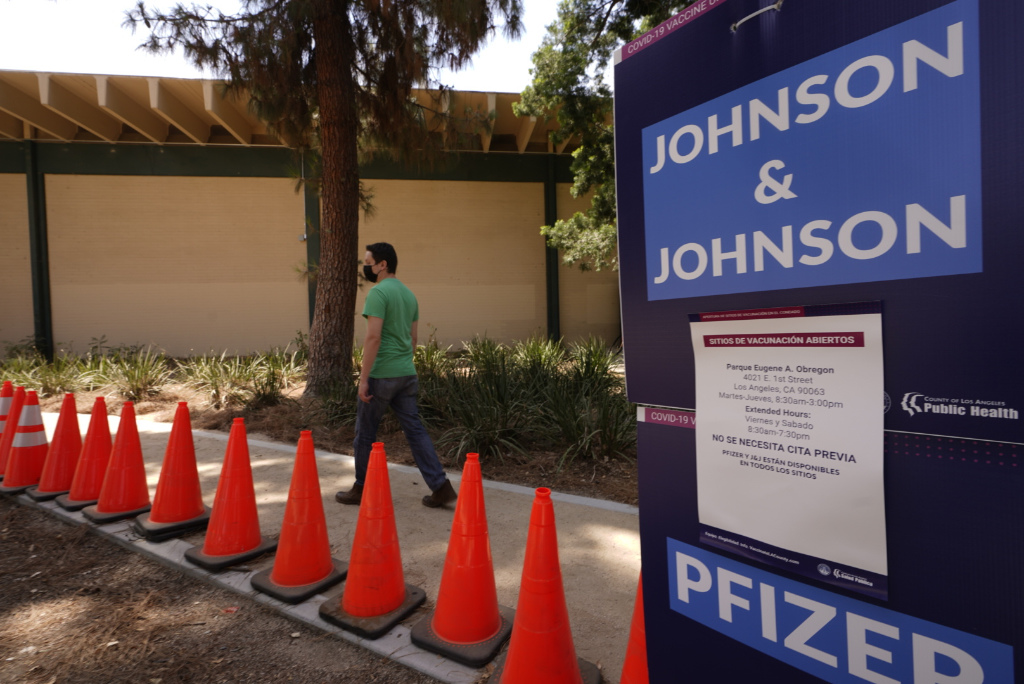 A man in a green shirt arrives for his appointment to get vaccinated, as banners advertise the availability of the Johnson & Johnson and Pfizer COVID-19 vaccines at a county-run vaccination site at the Eugene A. Obregon Park in Los Angeles.