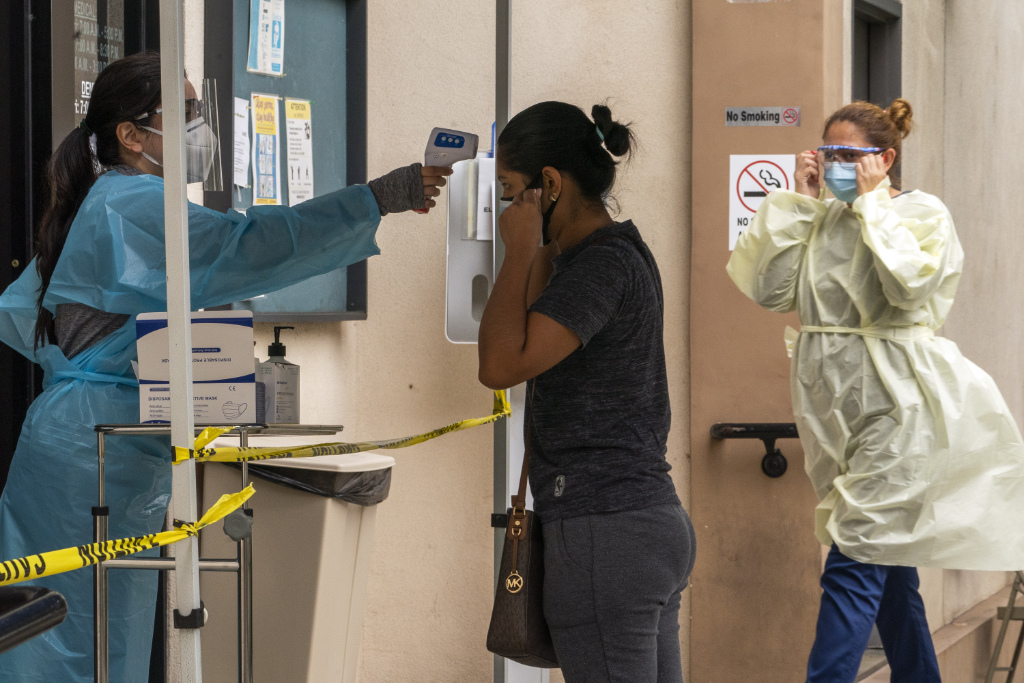 A patient has her body temperature screened after showing her COVID-19 vaccine card at the Clínica Monseñor Oscar A. Romero in the Pico-Union district of Los Angeles.