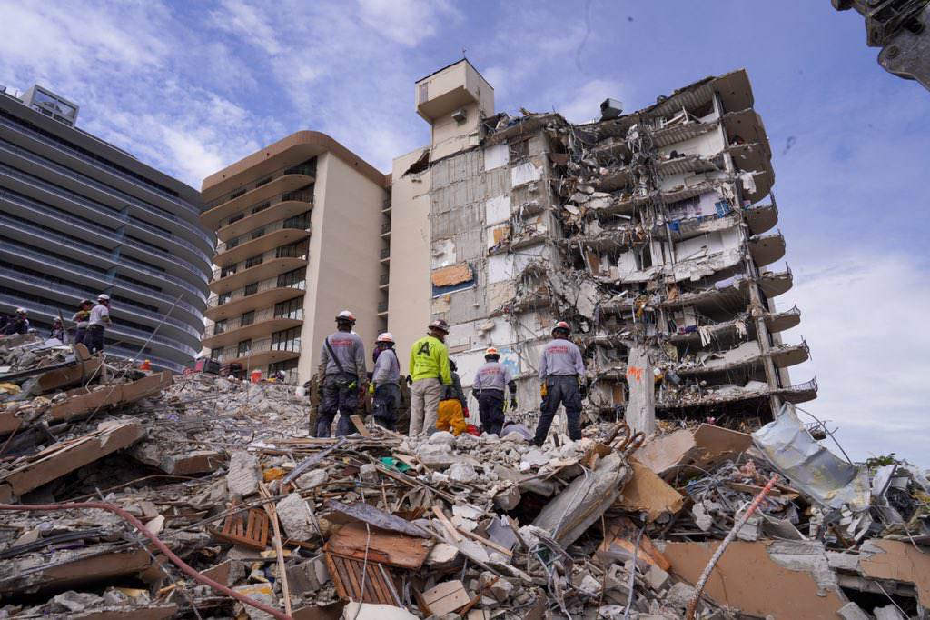 Rescue crews stand on top of a mountain of rubble with the remains of a collapsed building in front of them.