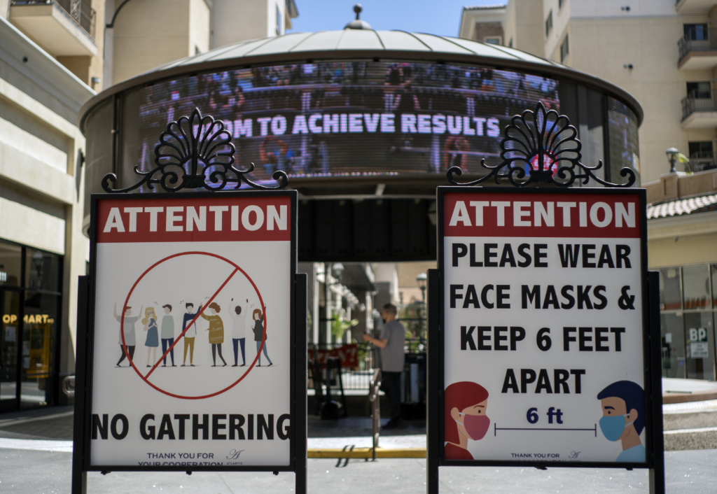 Signs with social distancing guidelines and face mask requirements are posted at an outdoor mall amid the COVID-19 pandemic in Los Angeles.
