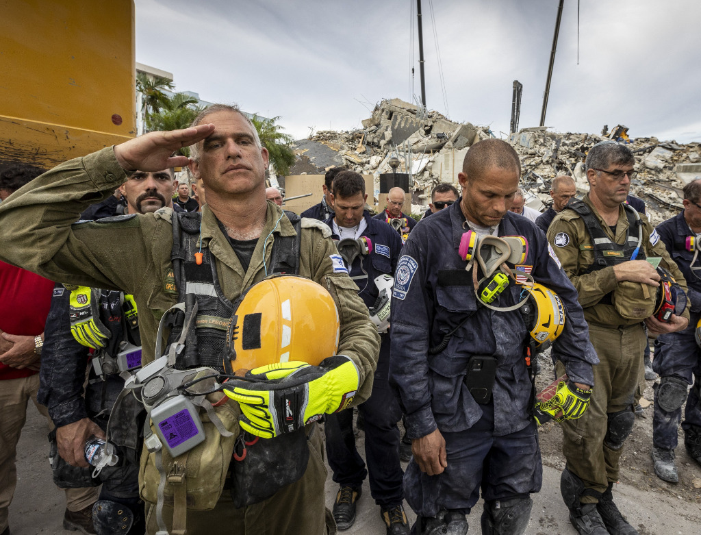 A member of the Israeli search and rescue team, left, salutes in front of the rubble that once was Champlain Towers South during a prayer ceremony