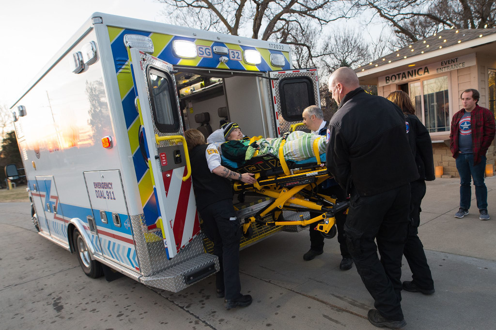 A man on a stretcher is loaded into the back of an ambulance.