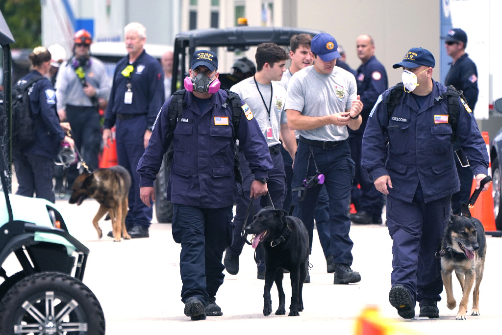 Rescue crews with dogs walk from the Champlain Towers South building.