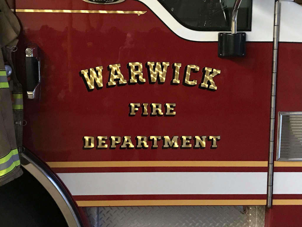 The side shows the side door with letters of the Warwick Fire Department.