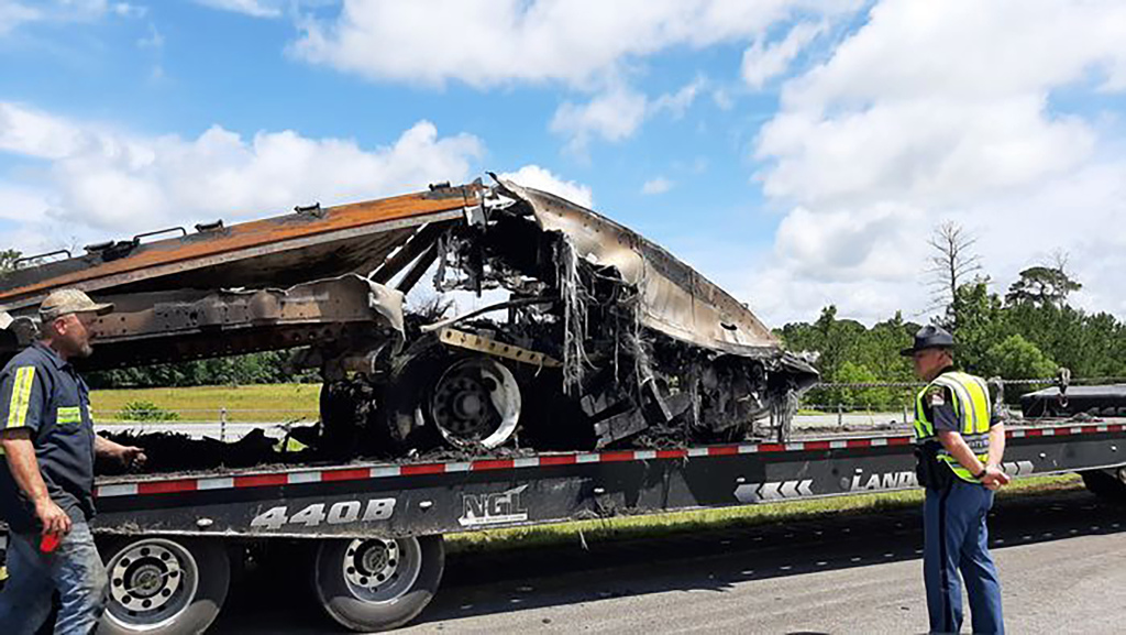 Some of the wreckage from a fatal multiple-vehicle crash a day earlier is loaded to be carried away, June 20, 2021, in Butler County, Ala.