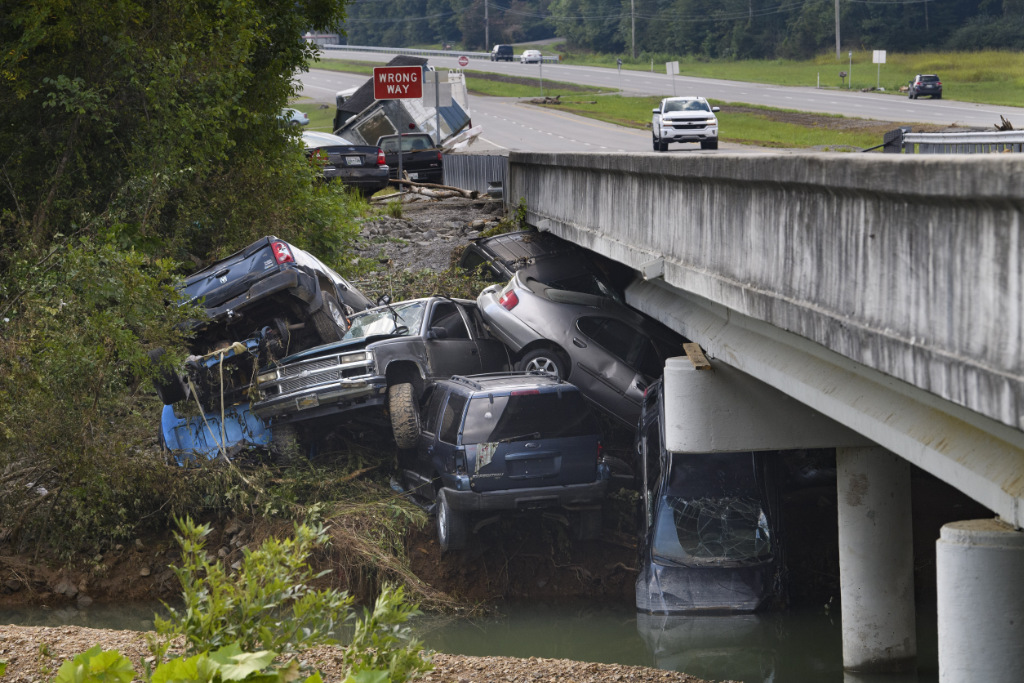 Cars are stacked on top of each other on the banks of Blue Creek being swept up in flood water, Monday, Aug. 23, 2021, in Waverly, Tenn.