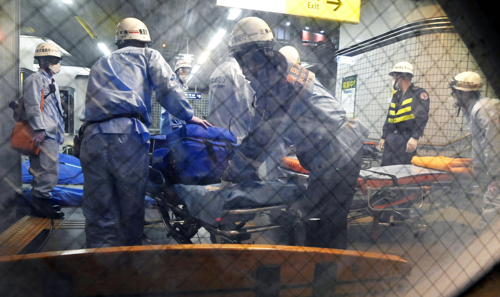 Rescuers papare stretchers at Soshigaya Okura Station after stabbing on a commuter train, in Tokyo Friday, Aug. 6, 2021.