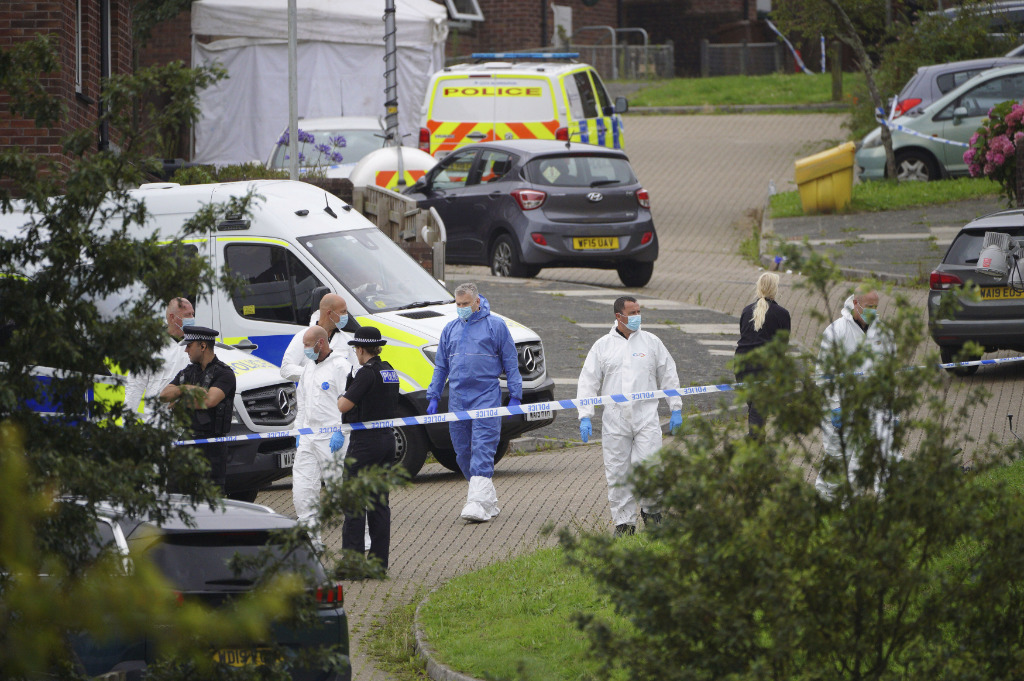 Forensic officers walk in Biddick Drive in the Keyham area of Plymouth, England Friday Aug. 13, 2021 where six people were killed in a shooting incident.