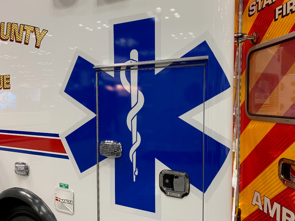 The photo shows the side of an ambulance with a blue Star of Life.
