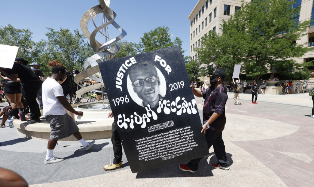 In this June 27, 2020, file photo, demonstrators carry a giant placard during a rally and march over the death of Elijah McClain outside the police department in Aurora, Colo.