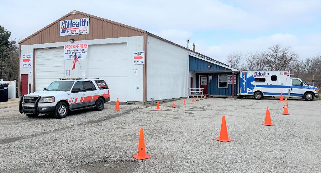 An inHealth ambulance and an SUV outside a garage.