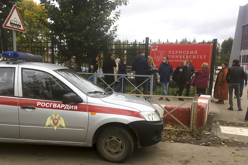 People stand behind the fence near the Perm State University, in Perm, Russia, Monday, Sept. 20, 2021.