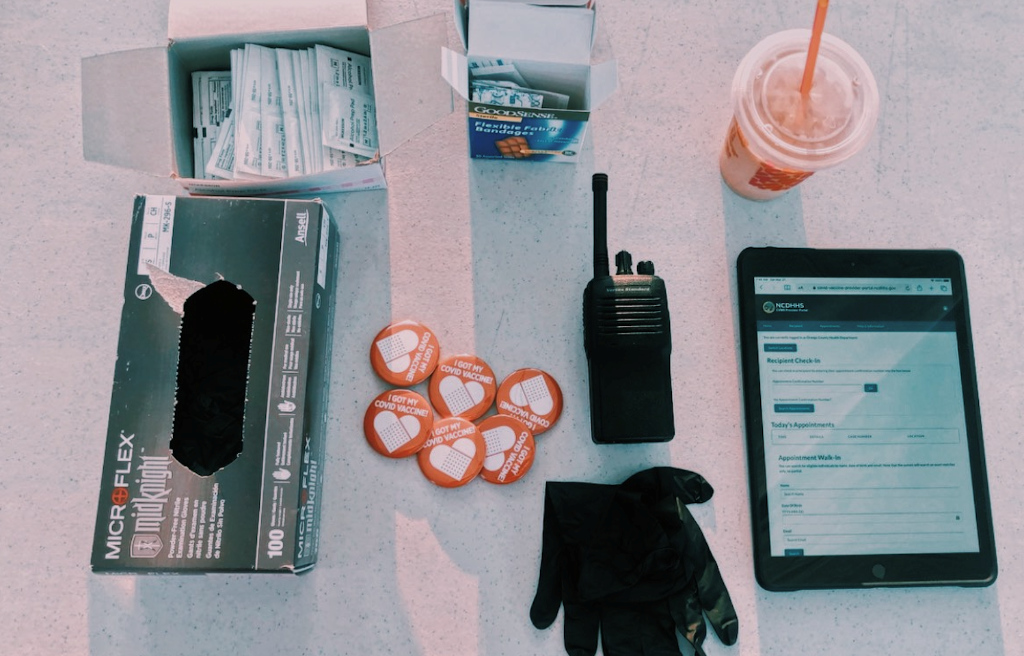 A picture of some EMS essentials: gauze pads, gloves, a radio and coffee.