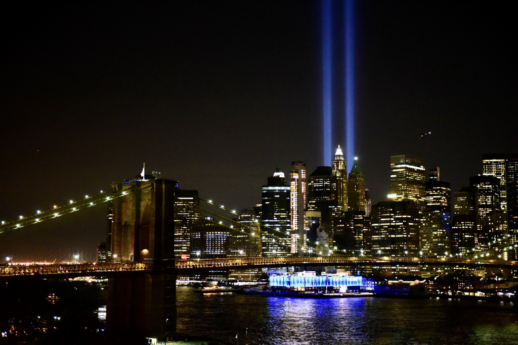 Twin light beams reach for the sky over New York City at night.