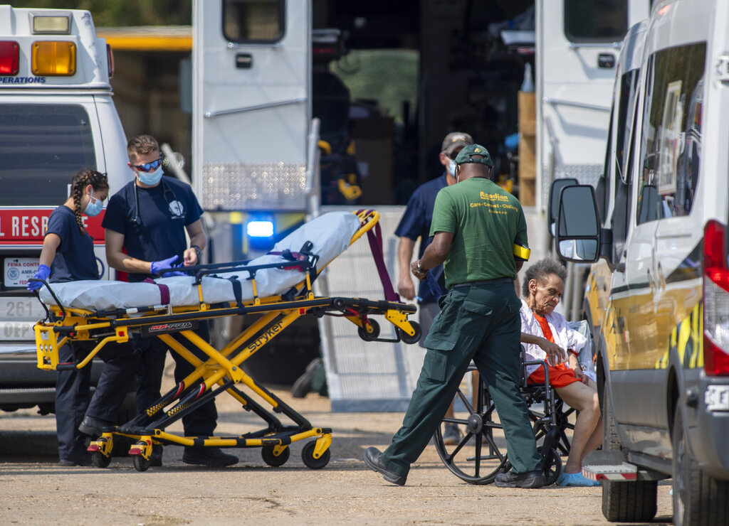 Paramedics standby at a mass shelter where about 800 residents were reportedly packed into a warehouse for Hurricane Ida, Thursday, Sept 2, 2021, in New Orleans.